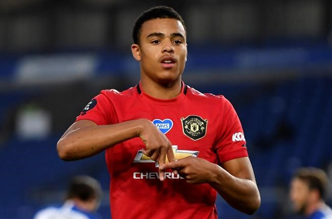 FILE - In this Tuesday, June 30, 2020 file photo, Manchester United's Mason Greenwood celebrates after scoring the opening goal of his team during the English Premier League soccer match between Brighton & Hove Albion and Manchester United at the AMEX Stadium in Brighton, England. England players Phil Foden and Mason Greenwood have been dropped for Tuesday's game against Denmark after breaching coronavirus rules in Iceland. They will return to England from Reykjavik rather than traveling to Copenhagen on Monday Sept. 7, 2020, after social media video was published in Iceland purporting to show the players meeting women from outside the team bubble. (Mike Hewitt/Pool via AP, File)