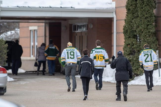Community members wearing jerseys enter St. Augustine Church prior to a memorial service for Brody Hinz, the Humboldt Broncos statistics compiler, who one of 16 people killed in a bus crash on April 6th 2018, in Humboldt, Sask., Saturday, April 14, 2018. THE CANADIAN PRESS/Liam Richards