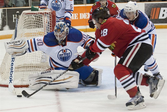 Edmonton Oilers goalie Olivier Roy pushes a puck out of the reach of Chicago Blackhawks forward Ben Smith during the third period of an NHL pre-season hockey game in Saskatoon on Tuesday, Sept 20, 2011. The Oilers defeated the Blackhawks 4-2. THE CANADIAN PRESS/Liam Richards