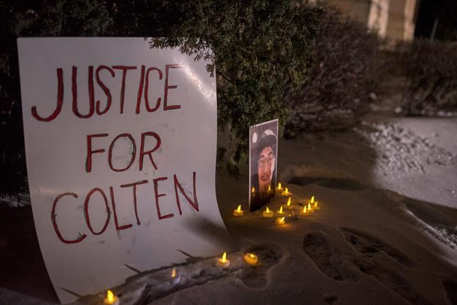 A sign and photo of Colten Boushie sits in front of the Court of Queen's Bench on the day of closing arguments and first day of jury deliberation in the trial of Gerald Stanley, the farmer accused of killing the 22-year-old Indigenous man, in Battleford, Sask., Thursday, February 8, 2018. THE CANADIAN PRESS/Liam Richards