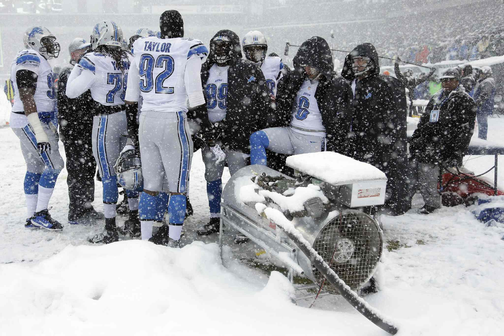 Detroit Lions players warm themselves during the first half.