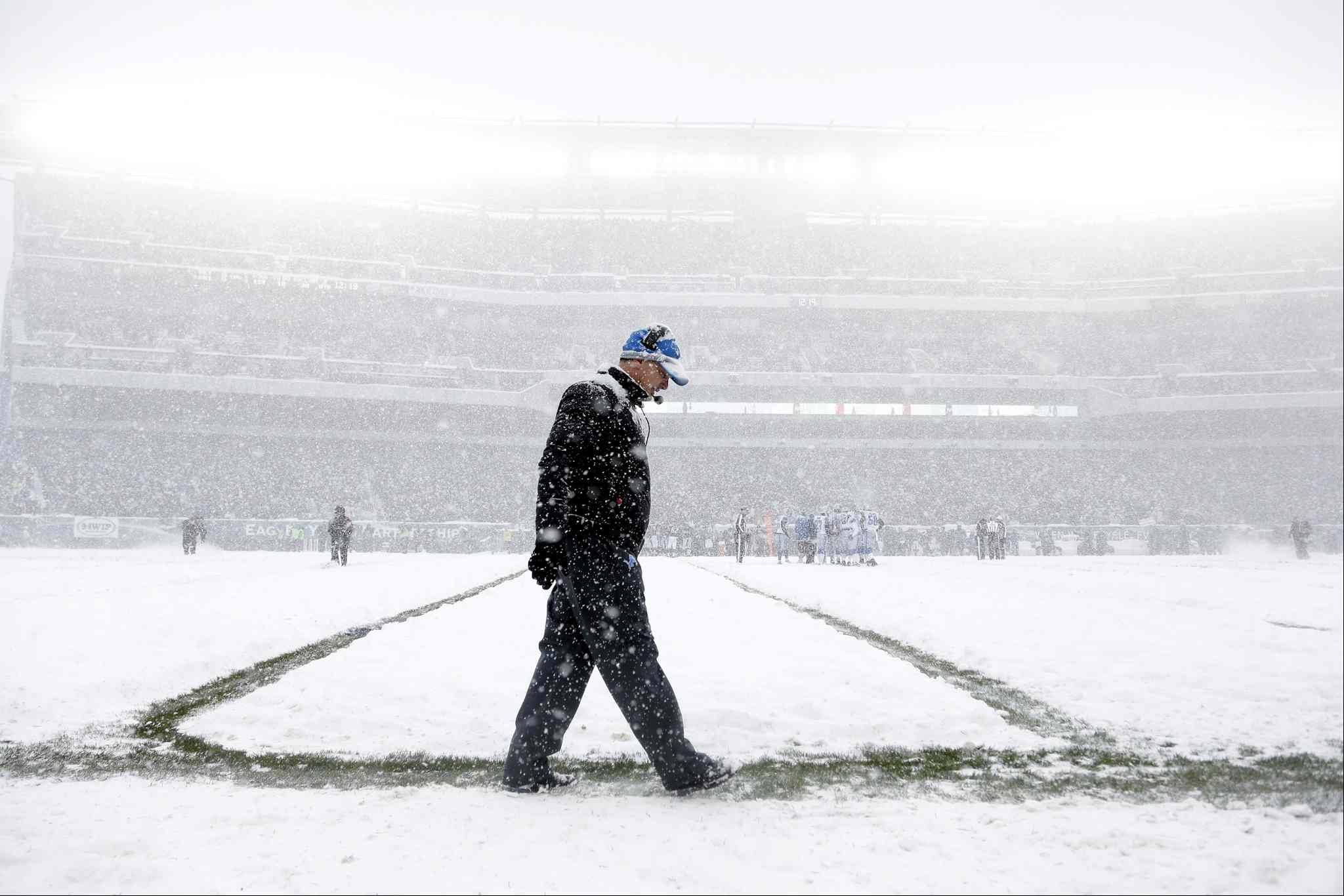 Detroit Lions head coach Jim Schwartz walks the sidelines as snow falls.