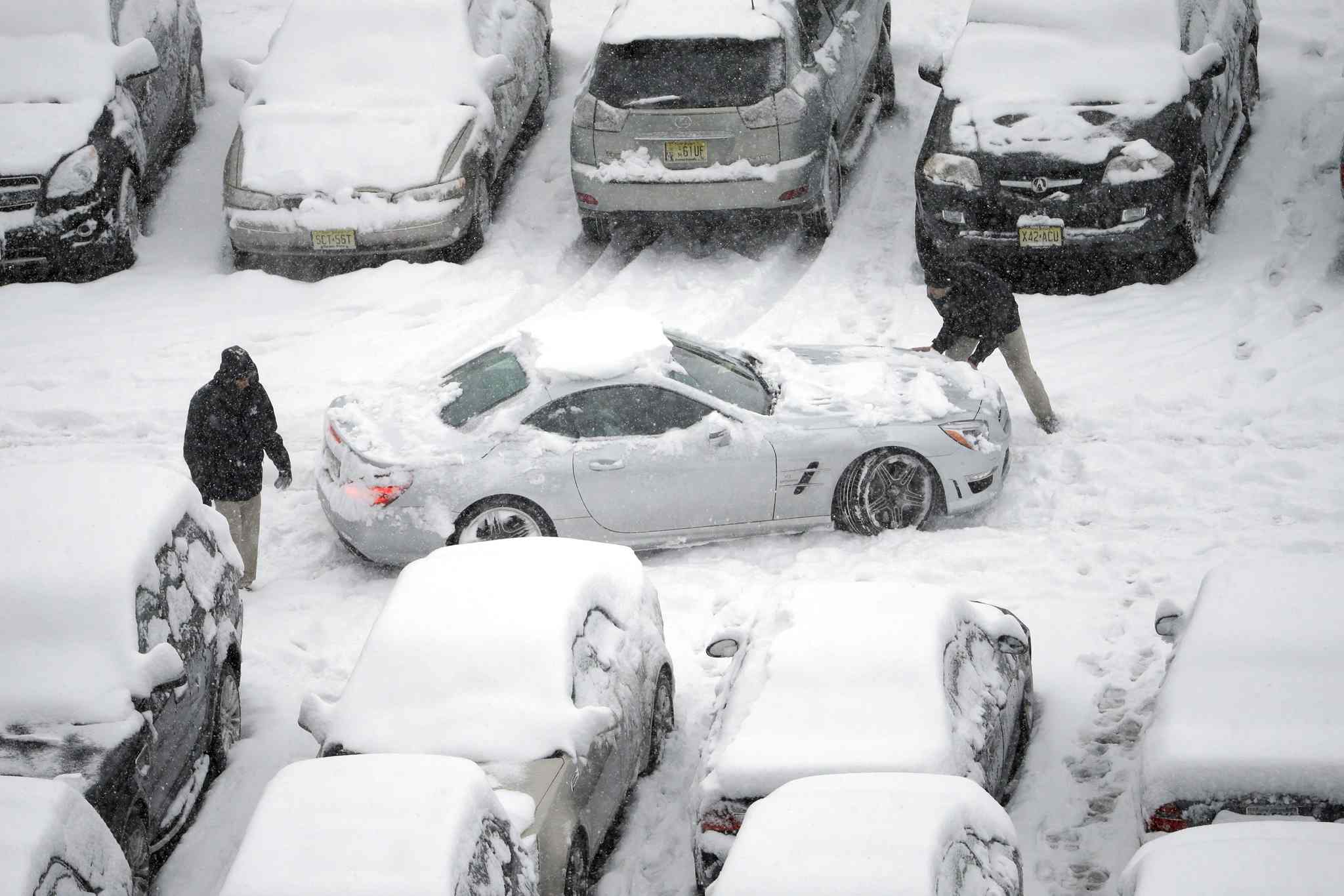 Snow-covered cars occupy a parking lot at Lincoln Financial Field in Philadelphia on Sunday.