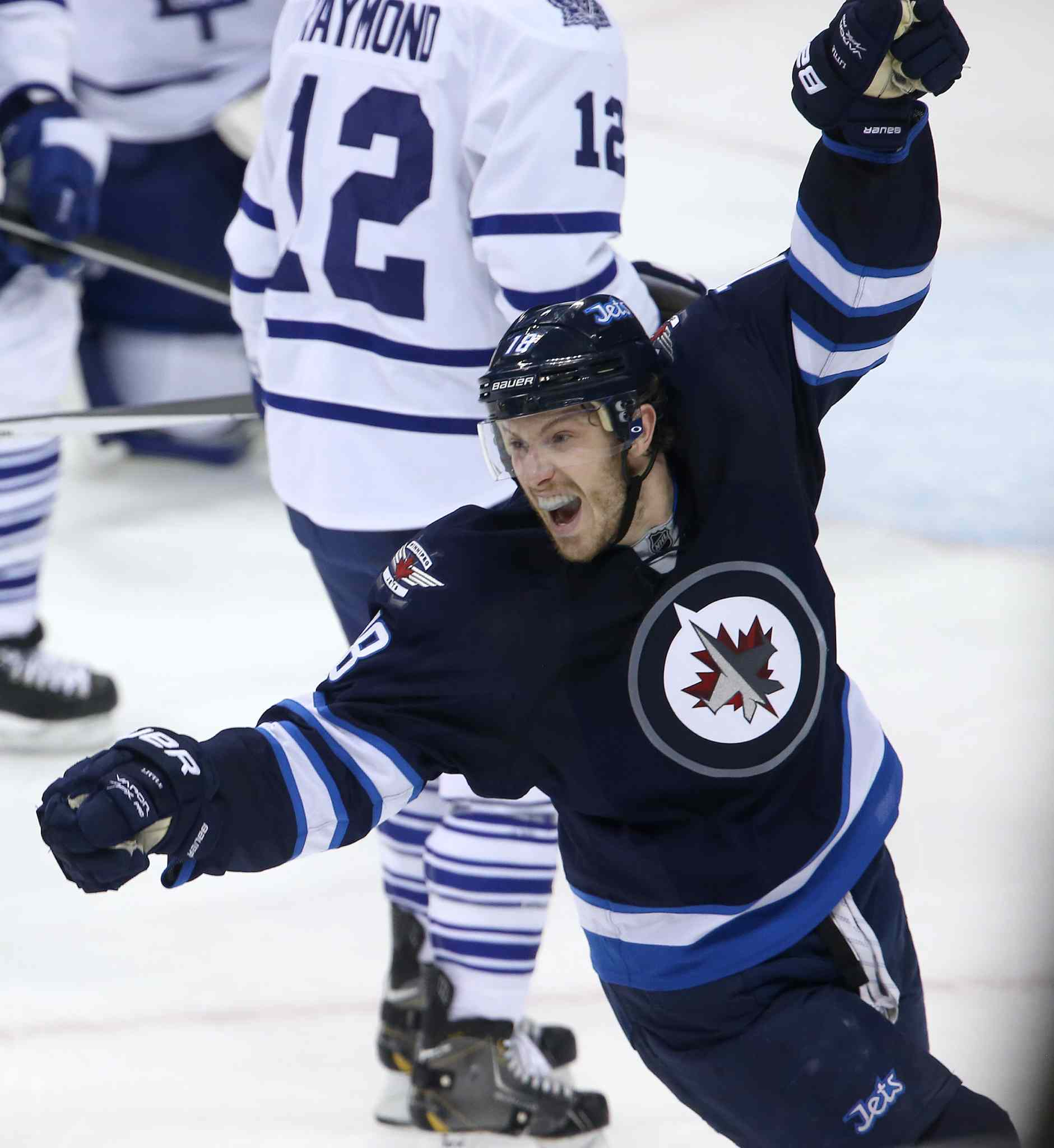 Winnipeg Jets' Bryan Little (18) celebrates after Dustin Byfuglien (33) scored to beat the Toronto Maple Leafs' during overtime on Saturday.