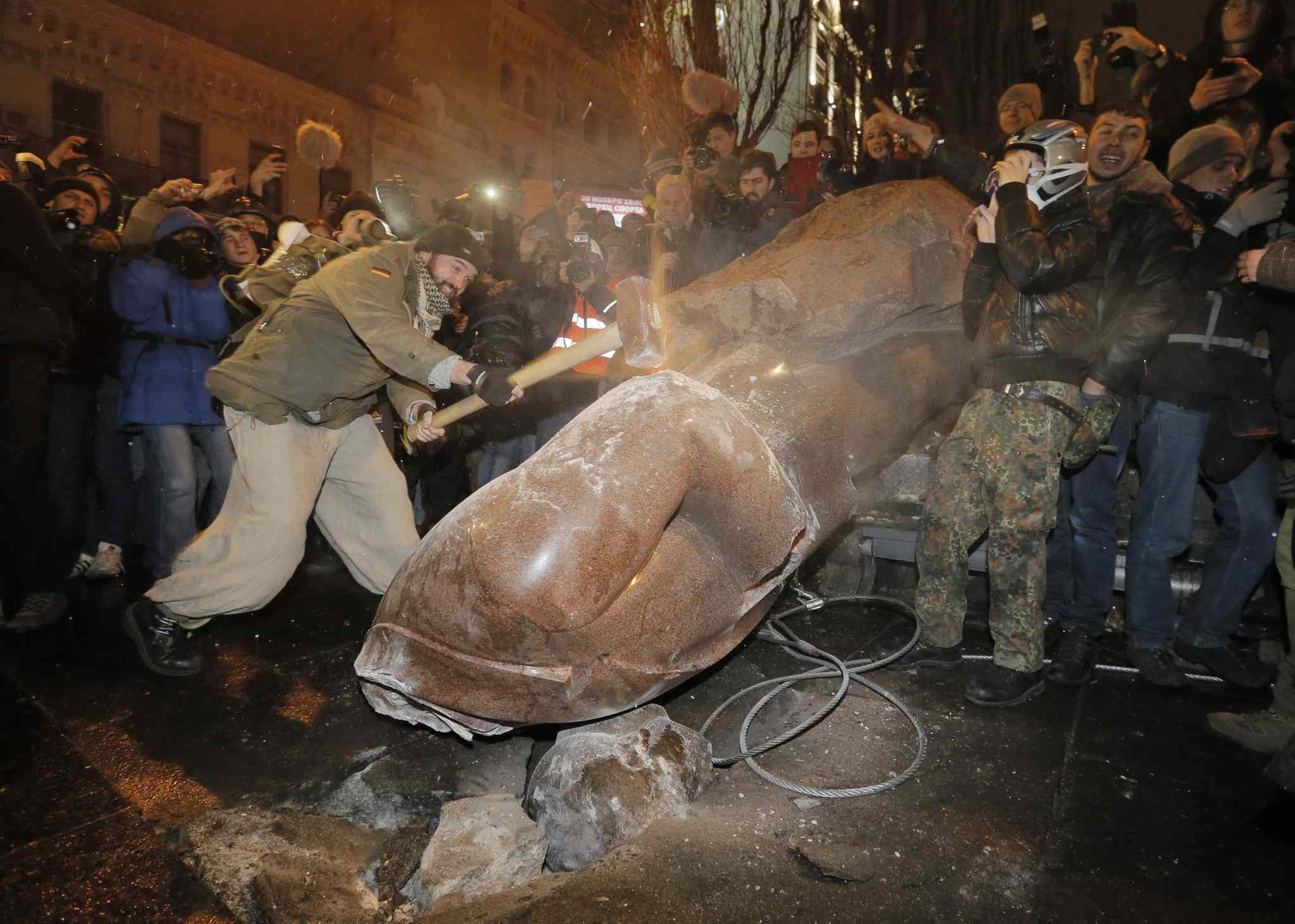 Ukrainian protesters smash a statue of Vladimir Lenin with a sledgehammer, in central Kyiv, Ukraine, Sunday. Anti-government protesters have toppled the statue of Bolshevik leader Vladimir Lenin in central Kiev amid huge protests gripping Ukraine. A group of protesters dragged down and decapitated the landmark statue Sunday evening after hundreds of thousands of others took to the streets to denounce the government's move away from Europe and toward Moscow.
