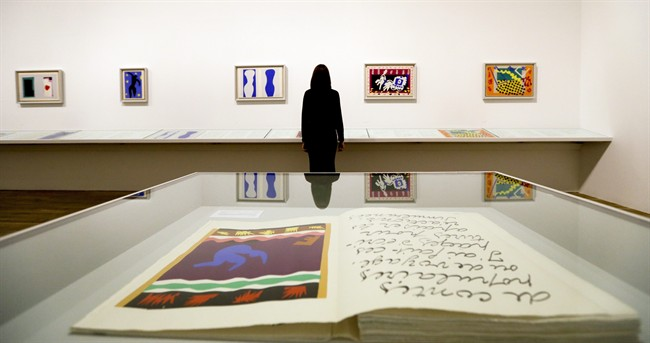 A woman is reflected in a glass cabinet as she looks at artworks by Henri Matisse, on display during a media opportunity at The Tate Modern in London, Monday, April 14, 2014. The artworks are part of the 'Henri Matisse: The Cut-Outs' exhibition that runs at the gallery from April 17 until Sept. 7, 2014. (AP Photo/Kirsty Wigglesworth)