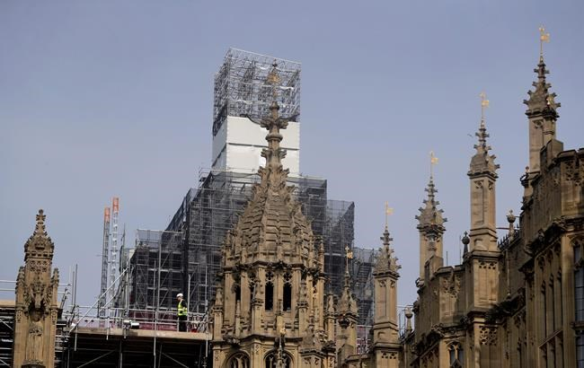 In this photo taken on Wednesday, April 17, 2019, Britain's Houses of Parliament, covered in hoarding and scaffolding as it undergoes restoration work to repair the crumbling building, in London. For some Britons who watched Notre Dame in Paris burn, horror was mixed with apprehension. What happened to the French landmark this week could befall the Houses of Parliament tomorrow. The seat of Britain's government is crumbling, leaky, infested with rodents, and a fire trap. (AP Photo/Kirsty Wigglesworth)
