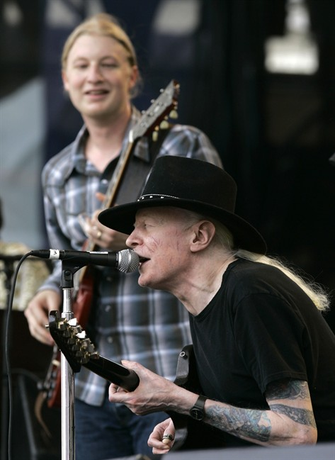 FILE - In this Saturday, July 28, 2007 file photo, Johnny Winter, seated, and Derek Trucks, background, perform