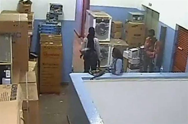 ADDS ADDITIONAL IDENTIFICATIONS - In this video image released by the Kenyan Defence Forces and made available by Citizen TV Friday Oct. 4 2013, men carrying automatic weapons and carrying bags are seen in the storeroom of the Nakumatt shop prior during the four-day-long siege at the Westgate Mall in Nairobi Kenya which killed more than 60 people last month. A Kenyan military spokesman has confirmed the names of four attackers as Abu Baara al-Sudani, unseen, Omar Nabhan, centre, Khattab al-Kene, left, and Umayr, right. (AP Photo/ Kenyan Defence forces via Citizen TV)
