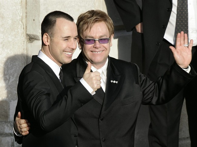 FILE - This is a Wednesday Dec. 21, 2005 file photo of pop star Elton John, right, and his longtime partner David Furnish, embrace as they wave to members of the media and the public after they had a civil ceremony at the Guildhall in the town of Windsor, England John and Furnish were the most prominent of hundreds of same-sex couples planning to form civil partnerships in England and Wales on Wednesday, the first day that such ceremonies become possible. With little fanfare or controversy, Britain announced Wednesday July 17, 2013 that Queen Elizabeth II _ hardly a social radical _ had signed into law a bill legalizing same-sex marriages in England and Wales. France has also legalized gay marriages, but only after a series of gigantic protests attracting families from the traditional heartland that revealed a deeply split society. (AP Photo/Lefteris Pitarakis)