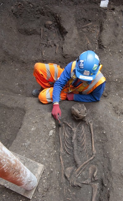 In this undated but recent photo supplied Friday March 15, 2015, by the London Crossrail Project, showing archaeologists working on the UK's largest infrastructure project, Crossrail, as they uncover an historical burial ground in central London. Scientists were called in to investigate bones found during the digging of a new railway in central London, after uncovered 13 skeletons were found. The skeletons will be tested to see if they died from the Black Death plague which killed between 30 and 60 percent of the European population in the 14th century, and scientist hope to map the DNA signature of the plague bacteria. (AP Photo / Crossrail Project)
