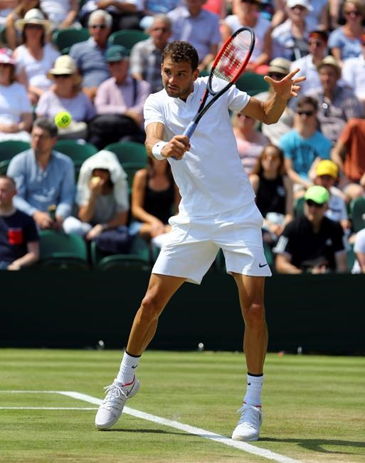 Bulgaria's Grigor Dimitrov makes a return to Marcos Baghdatis of Cyprus during their Men's Singles Match at the Wimbledon Tennis Championships in London Thursday