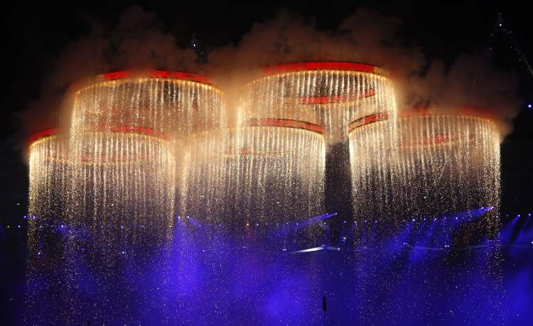 The Olympic rings are illuminated with pyrotechnics as they are raised above the stadium during the Opening Ceremony at the 2012 Summer Olympics, Friday, July 27, 2012, in London.  (Jae C. Hong / The Associated Press)