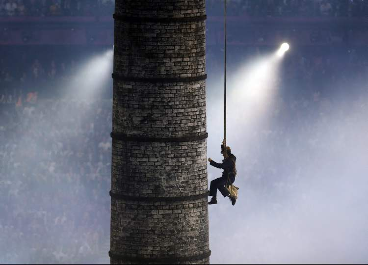 A performer scales a representation of a smoke stack during the Opening Ceremony at the 2012 Summer Olympics, Friday, July 27, 2012, in London. (Charlie Riedel / The Associated Press)