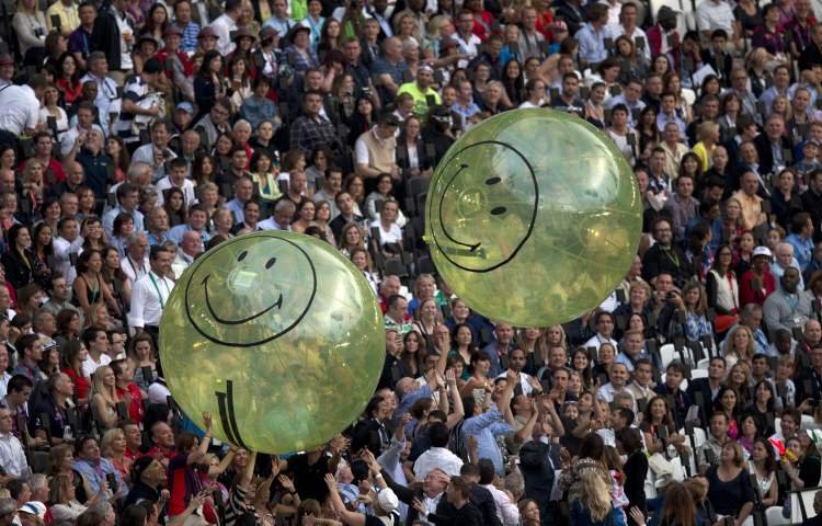 Spectators play with giant smiley face beach balls during the pre-show for the Olympic Games Opening ceremonies in London on Friday July 27, 2012.