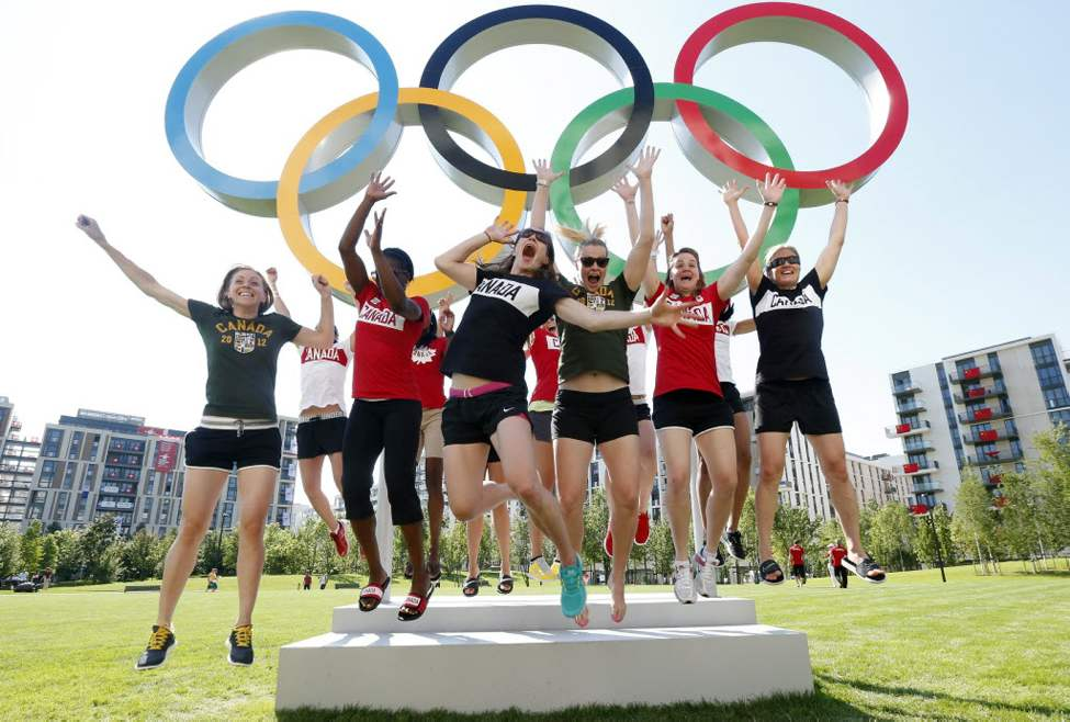 Canada's basketball team members jump in the air in front of the Olympic rings inside the London 2012 Olympic Village in Stratford, east London. (AP Photo/Suzanne Plunkett, Pool)
