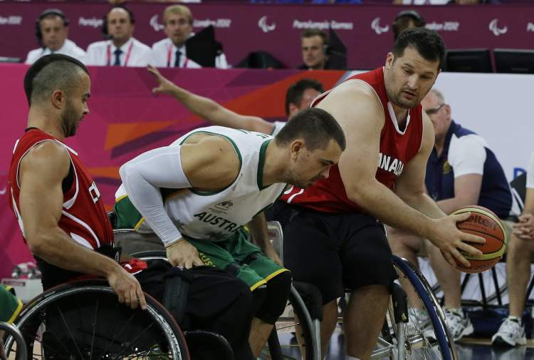 Canada's Joey Johnson, right, controls the ball during the men's wheelchair basketball gold medal game against Australia at the 2012 Paralympics in London in September 2012.