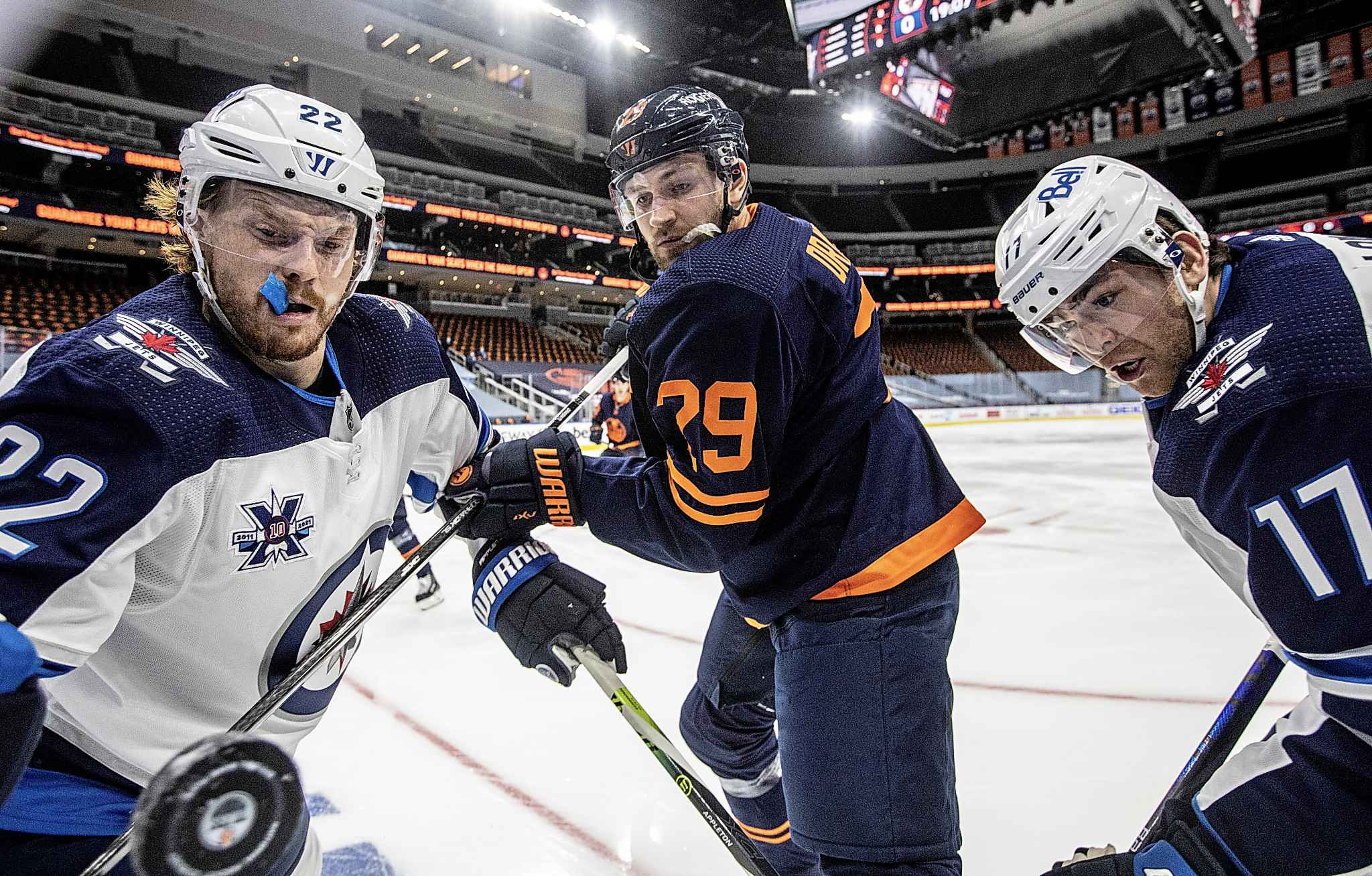 Edmonton Oilers' Leon Draisaitl and Winnipeg Jets' Mason Appleton and Adam Lowry battle for the puck during the first period. THE CANADIAN PRESS/Jason Franson