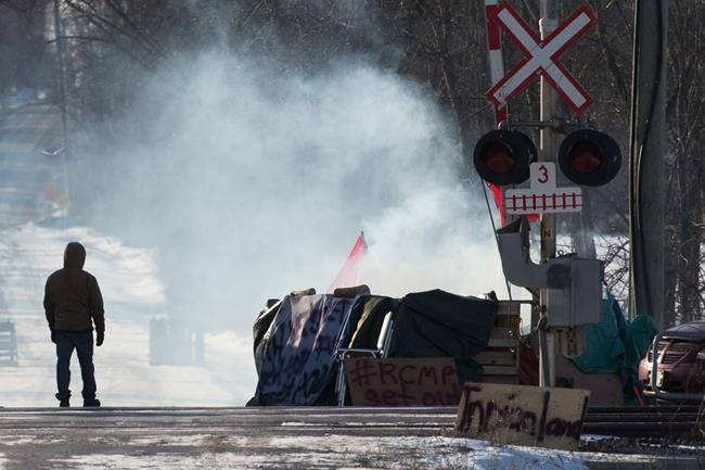 A protester stands beside smoke at the closed train tracks in Tyendinaga Mohawk Territory near Belleville, Ont., on Thursday Feb. 20, 2020, as they protest in solidarity with the Wet'suwet'en hereditary chiefs opposed to the LNG pipeline in northern British Columbia. A group of hereditary leaders from the Wet'suwet'en First Nation in B.C. is to spend the day with Mohawk supporters in Ontario. THE CANADIAN PRESS/Lars Hagberg