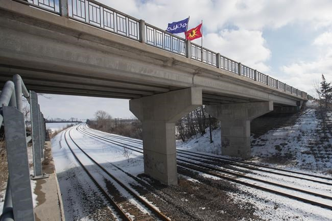 A Six Nations flag, left, and a Mohawk warrior flag fly on a bridge over the closed train tracks in Tyendinaga Mohawk Territory, Ont. on Wednesday, Feb. 12, 2020, in support of Wet'suwet'en's blockade of a natural gas pipeline in northern B.C. THE CANADIAN PRESS/Lars Hagberg