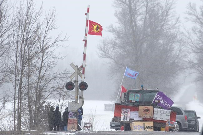 Protesters stand on the closed train tracks during a rail blockade in Tyendinaga Mohawk Territory, Ont. on Thursday, Feb.13, 2020, in solidarity with the Wet'suwet'en hereditary chiefs opposed to the LNG pipeline in northern British Columbia. THE CANADIAN PRESS/Lars Hagberg