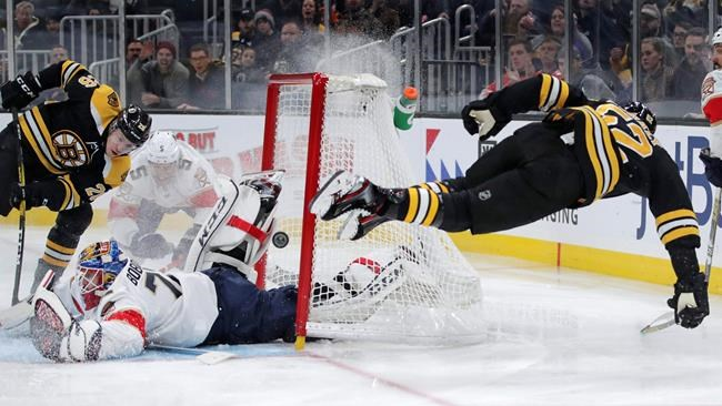 Florida Panthers goaltender Sergei Bobrovsky (72) makes a save on a shot by Boston Bruins center Sean Kuraly (52), who goes airborne after colliding with the net, during the second period of an NHL hockey game in Boston, Tuesday, Nov. 12, 2019. At left is Boston Bruins center Par Lindholm. (AP Photo/Charles Krupa)