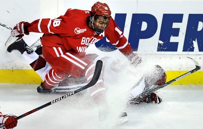 Boston University forward Jordan Greenway (18) drops Harvard defenseman Wiley Sherman to the ice as they chase the puck during the first period of the first round of the Beanpot hockey tournament in Boston, Monday, Feb. 5, 2018. (AP Photo/Charles Krupa)
