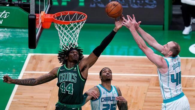 Boston Celtics center Robert Williams III (44) and Charlotte Hornets center Cody Zeller (40) battle for a rebound during the first half of an NBA basketball game, Wednesday, April 28, 2021, in Boston. (AP Photo/Charles Krupa)