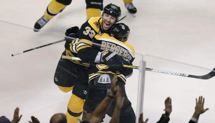 Boston Bruins centre Patrice Bergeron is embraced by teammate Zdeno Chara after scoring the game-winning goal in overtime Monday in Boston.
