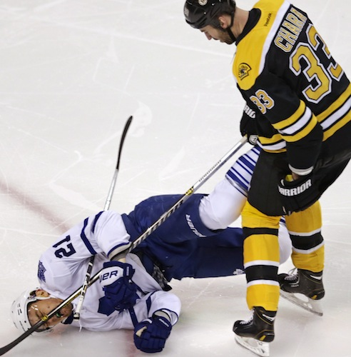 Boston Bruins defenceman Zdeno Chara looks down at Toronto Maple Leafs winger James van Riemsdyk after doing what he arguably does best — laying a bone-rattling hit. (Charles Krupa / The Associated Press)