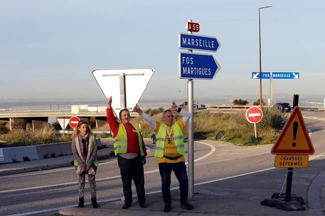 A group of demonstrators wearing their yellow vest joke as they occupy a traffic circle, Wednesday, Dec. 5, 2018 outside La Mede oil refinery, near Martigues, southeastern France. Trade unions and farmers pledged Wednesday to join nationwide protests against President Emmanuel Macron, as concessions by the government failed to stem the momentum of the most violent demonstrations France has seen in decades. (AP Photo/Claude Paris)