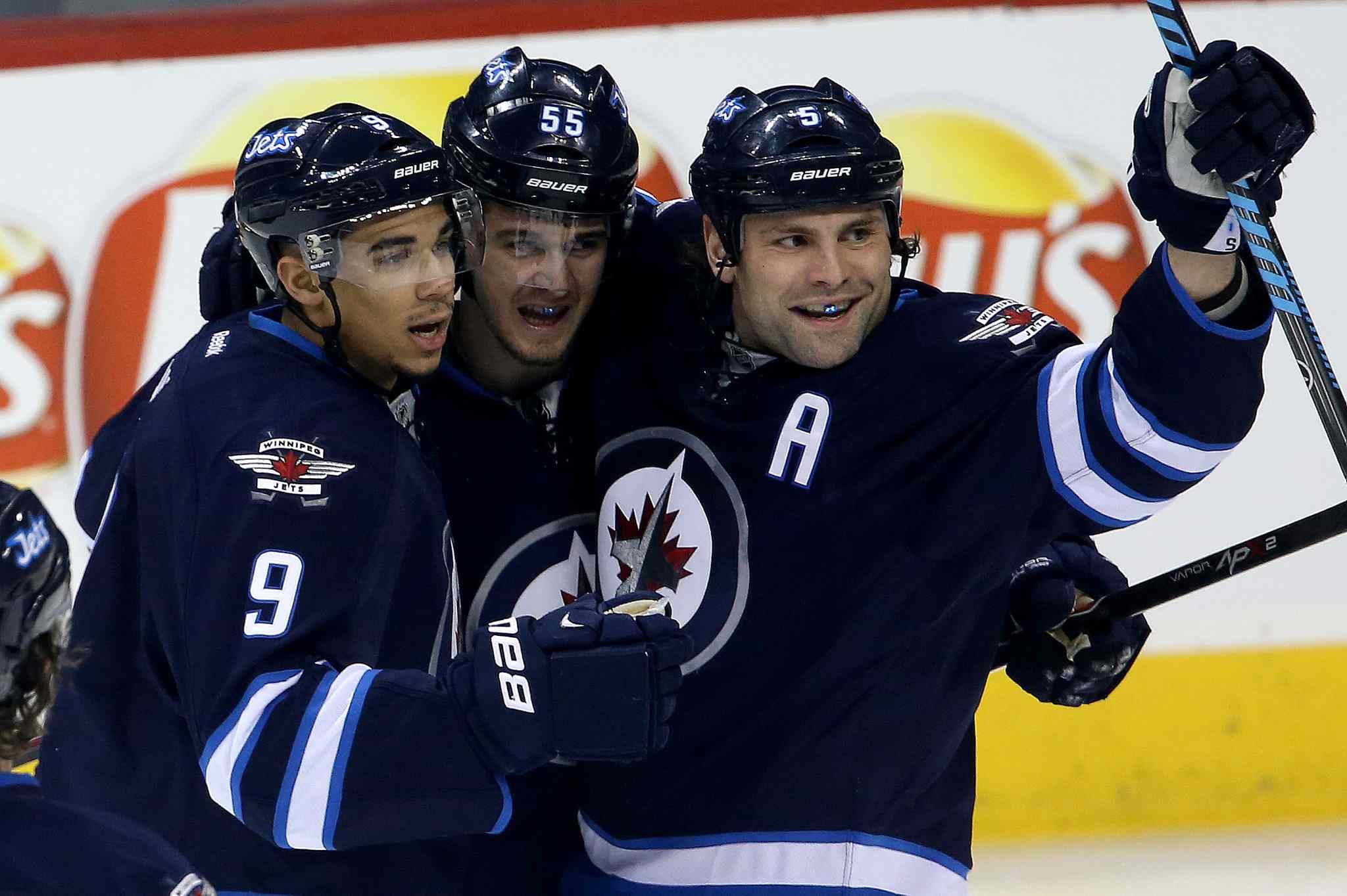 Winnipeg Jets' Evander Kane (9), Mark Scheifele (55) and Mark Stuart (5) celebrate after Scheifele opened the scoring against the Toronto Maple Leafs at MTS Centre in Winnipeg on Saturday. The Jets won in overtime 5-4.