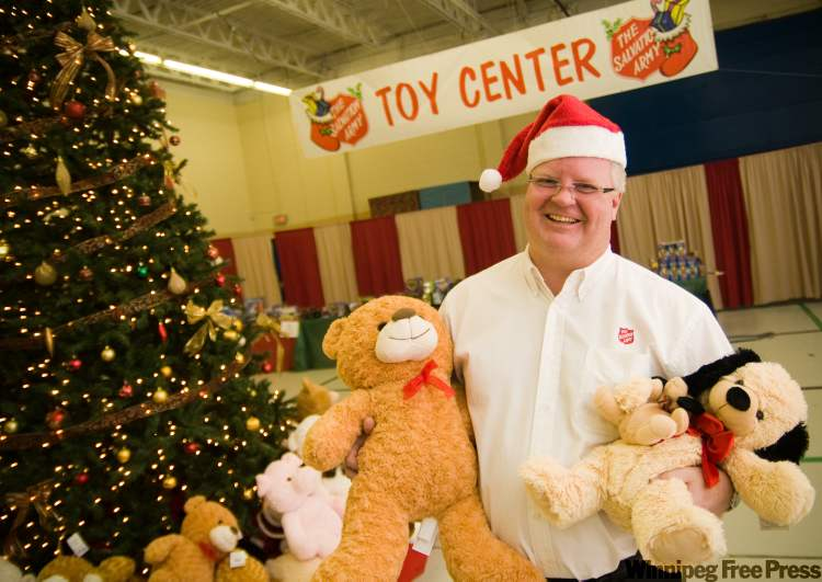 Salvation Army Weetamah Centre ministry director Mark Young cuddles a couple of furry companions Tuesday at Toy Mountain, the Sally Ann toy depot at 324 Logan Ave.