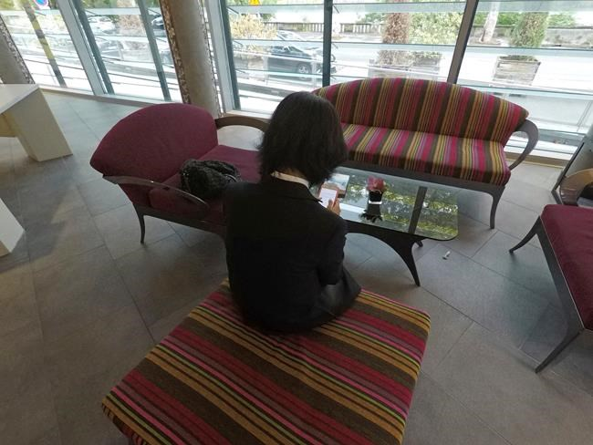 Grace Meng, the wife of missing Interpol President Meng Hongwei, who does not want her face shown, consults her mobile phone in the lobby of a hotel in Lyon, central France, where the police agency is based, on Sunday Oct. 7, 2018. Interpol said Saturday it has made a formal request to China for information about the agency's missing president, a senior Chinese security official who seemingly vanished while on a trip home. (AP Photo/John Leicester)