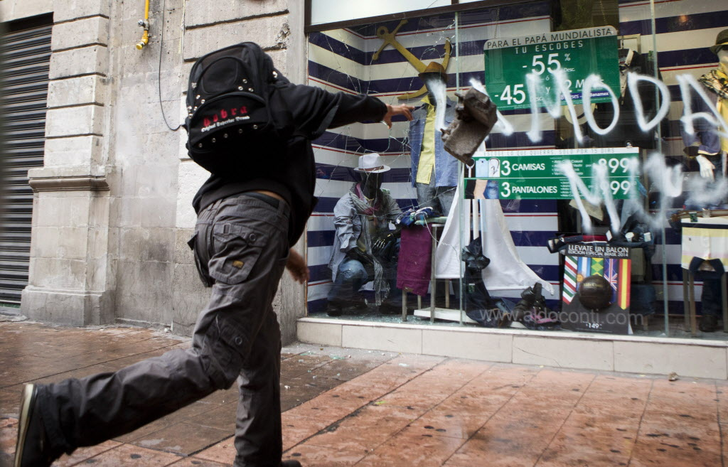 An anarchist smashes a store window during a May Day march by anarchists in Mexico City. Thousands of people, many calling for greater worker rights and protections, participated in various marches around the city centre.