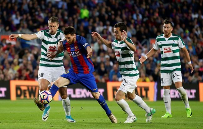 FC Barcelona's Lionel Messi second left duels for the ball during the Spanish La Liga soccer match between FC Barcelona and Eibar at the Camp Nou stadium in Barcelona Spain Sunday