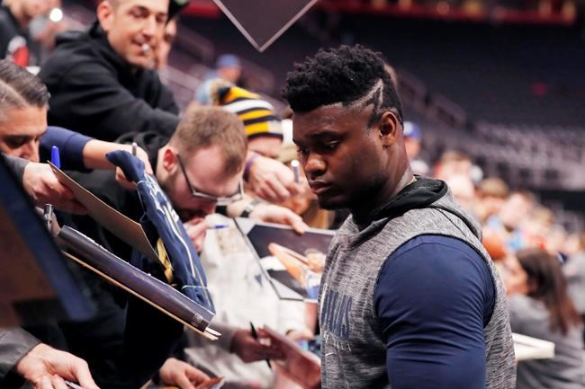 New Orleans Pelicans forward Zion Williamson signs autographs during warmups of an NBA basketball game against the Detroit Pistons, Monday, Jan. 13, 2020, in Detroit. (AP Photo/Carlos Osorio)