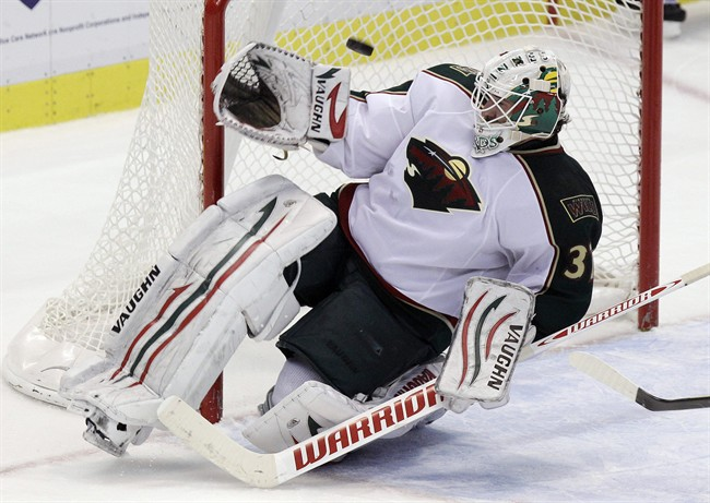 Minnesota Wild goalie Josh Harding (37) deflects a shot during the third period of an NHL hockey game against the Detroit Red Wings in Detroit, Tuesday, Nov. 1, 2011. Harding had 37 saves in the Wild's 2-1 overtime win. (AP Photo/Carlos Osorio)