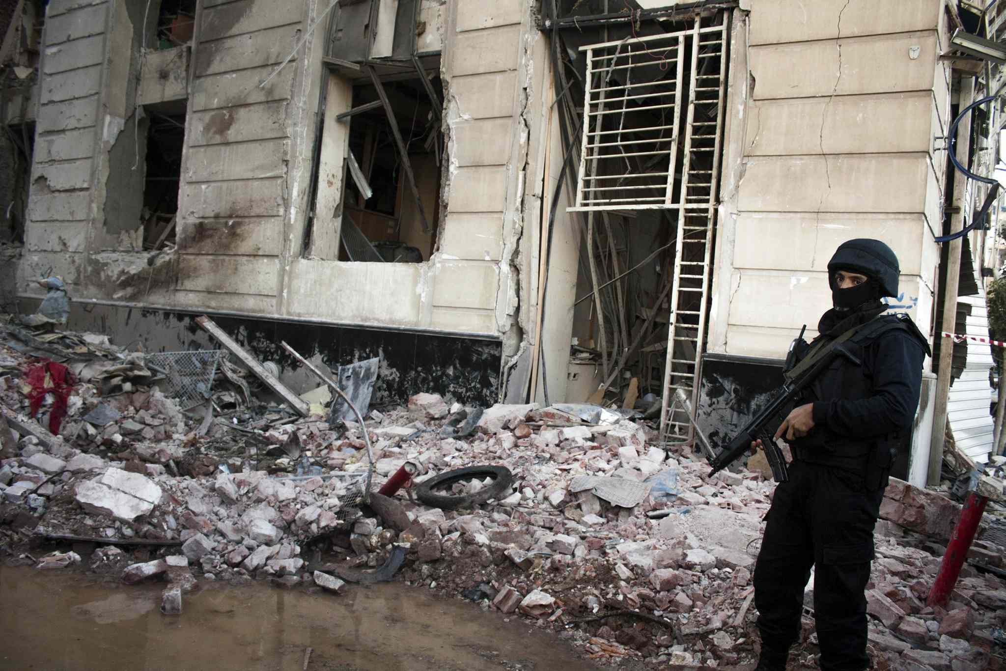 An officer guards the scene of a fatal car bombing outside a security headquarters building in Mansoura, Egypt, on Tuesday.
