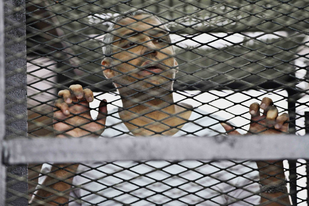 Mohammed Fahmy, Canadian-Egyptian acting bureau chief of Al-Jazeera, appears in a defendant's cage along with several other defendants during their trial on terror charges at a courtroom in Cairo, Egypt. An Egyptian court has convicted three journalists for Al-Jazeera English on Monday, June 23, 2014, including Egyptian-Canadian Mohamed Fahmy, and sentenced them to seven years in prison each on terrorism-related charges.