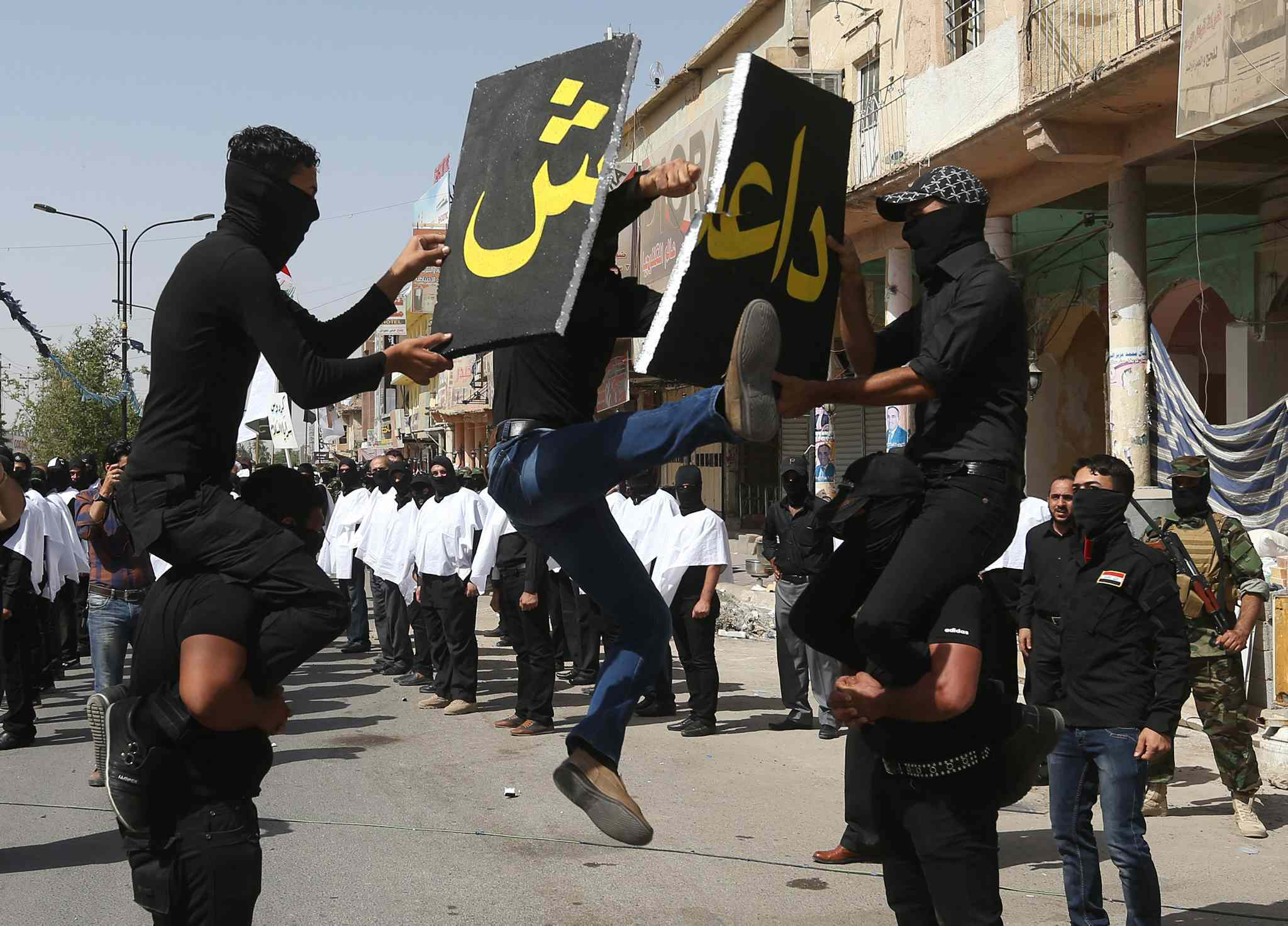 An Iraqi Shiite militiaman, a follower of Shiite cleric Muqtada al-Sadr, jumps to break a placard with the name of the Islamic State of Iraq and the Levant (ISIL) during a parade, in the northern oil rich province of Kirkuk, Iraq, Saturday, June 21, 2014.