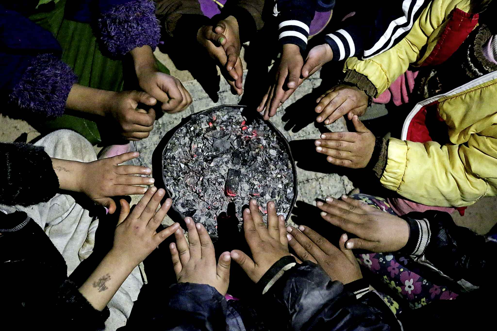 In this 2014 photo, children from Yazidi families displaced by Islamic State group militants warm their hands over hot coals in Dohuk, northern Iraq. (Seivan Selim / Associated Press files)