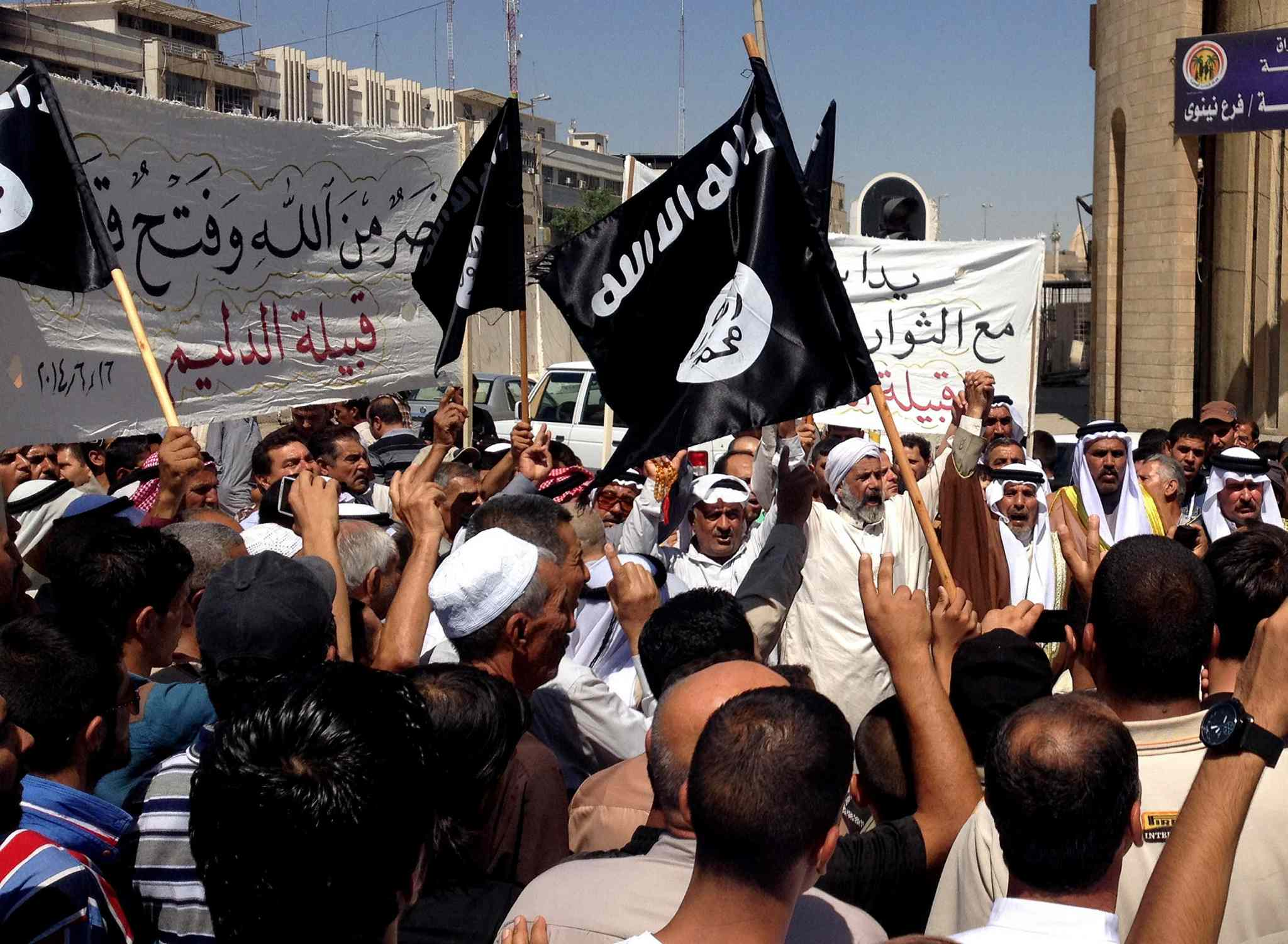 In this June 16, 2014 file photo, demonstrators chant pro-al-Qaida-inspired Islamic State of Iraq and the Levant (ISIL) as they wave al-Qaida flags in front of the provincial government headquarters in Mosul, 360 kilometres northwest of Baghdad, Iraq.