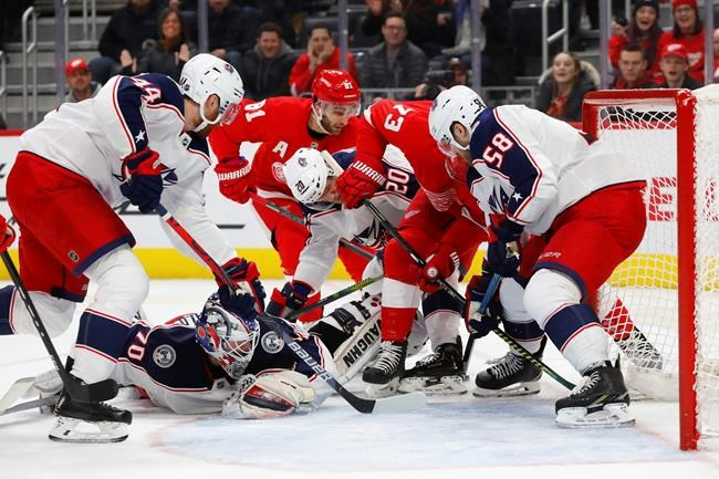Columbus Blue Jackets defenseman David Savard (58) keeps the puck out of the net as goaltender Joonas Korpisalo (70) is out of position against the Detroit Red Wings in the second period of an NHL hockey game Tuesday, Dec. 17, 2019, in Detroit. (AP Photo/Paul Sancya)