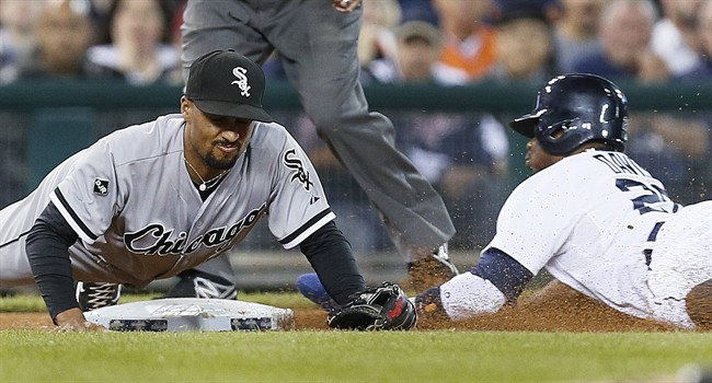 Detroit Tigers left fielder Rajai Davis, right, steals third base as Chicago White Sox third baseman Marcus Semien can't handle the throw in the fifth inning of a baseball game in Detroit Tuesday, Sept. 23, 2014. Davis scored on the overthrow. (AP Photo/Paul Sancya)