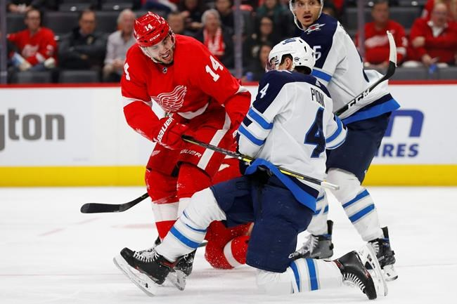Detroit Red Wings center Robby Fabbri (14) and Winnipeg Jets defenseman Neal Pionk (4) battle for position in the second period of an NHL hockey game Thursday, Dec. 12, 2019, in Detroit. (AP Photo/Paul Sancya)