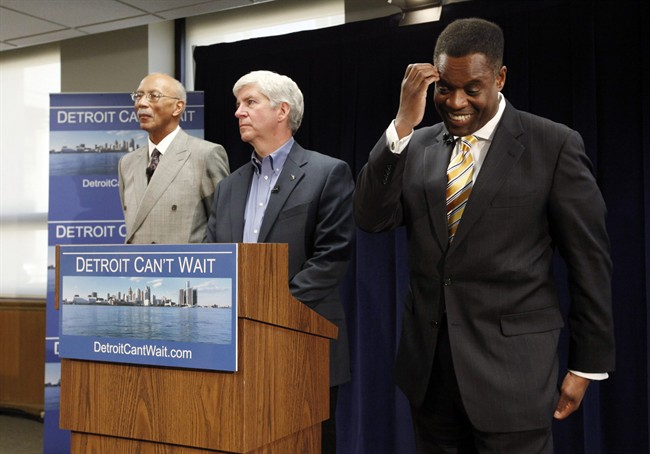 Kevyn Orr, right, reacts to a question as Detroit Mayor Dave Bing, left, and Gov. Rick Snyder, center, listen during a news conference in Detroit, Thursday, March 14, 2013. Snyder announced that he had chosen Orr, a partner in the Cleveland-based law and restructuring Jones Day firm, as Detroit's emergency manager. Snyder's already declared a financial emergency in Detroit, saying local officials lacked a plan to solve it. (AP Photo/Paul Sancya)