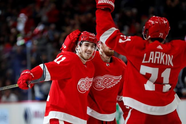 Detroit Red Wings right wing Filip Zadina (11) celebrates his goal with Filip Hronek (17) and Dylan Larkin (71) in the second period of an NHL hockey game against the Winnipeg Jets, Thursday, Dec. 12, 2019, in Detroit. (AP Photo/Paul Sancya)