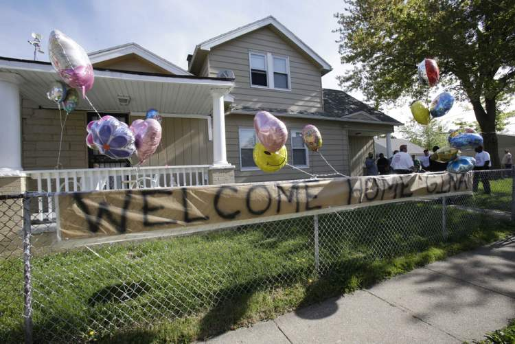 A welcoming sign hangs on a fence outside the home of Gina DeJesus Tuesday, May 7, 2013, in Cleveland.  (Tony Dejak / The Associated Press)