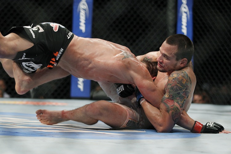 Sam Stout (left) takes down James Krause during their lightweight bout. (John Woods / The Canadian Press)